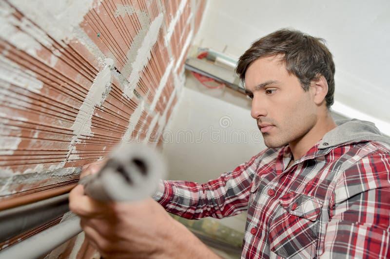 Homme mettant d'aplomb sa maison photographie stock libre de droits