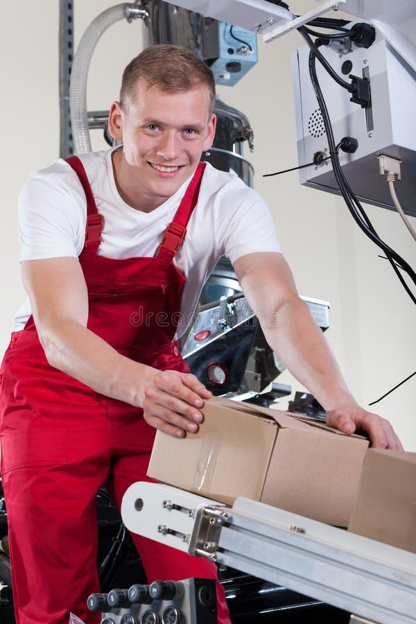 Homme mettant des boîtes sur la bande de conveyeur automatique photos stock