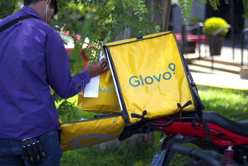 Homme mettant des sacs à l'intérieur d'une boîte de Glovo photo libre de droits