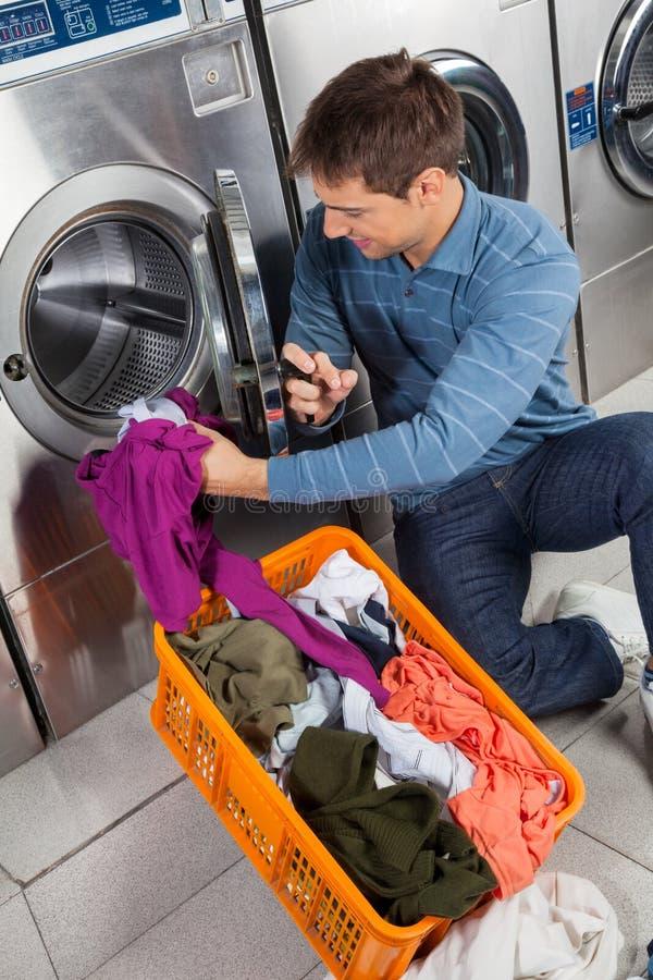 Homme mettant des vêtements dans la machine à laver photographie stock