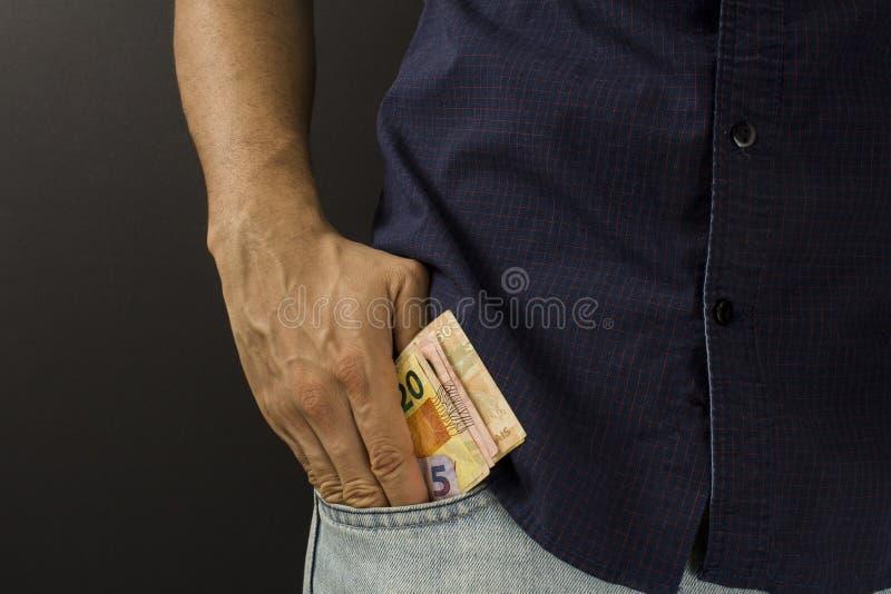 Homme mettant l'argent brésilien à l'intérieur de la poche photo libre de droits