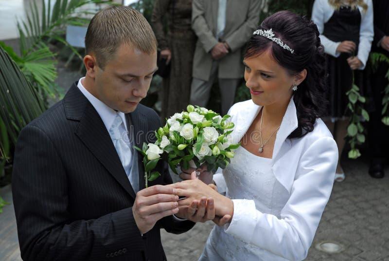 Homme mettant la boucle sur la mariée photographie stock
