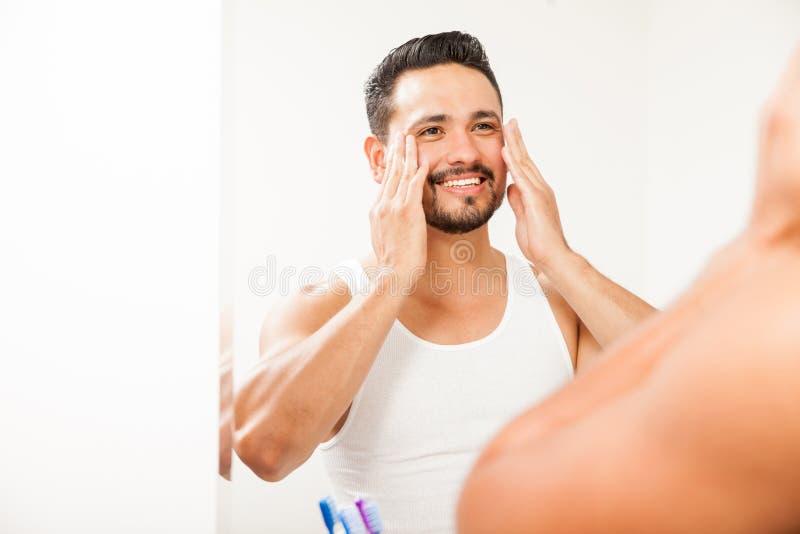 Homme mettant sur la crème sur son visage image stock