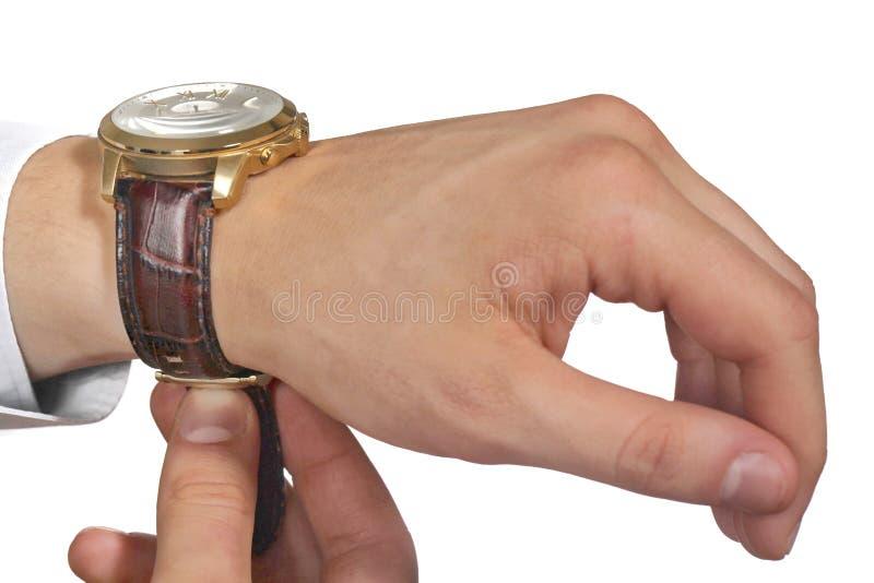 Homme mettant sur la montre-bracelet Isoalted sur le fond noir image stock