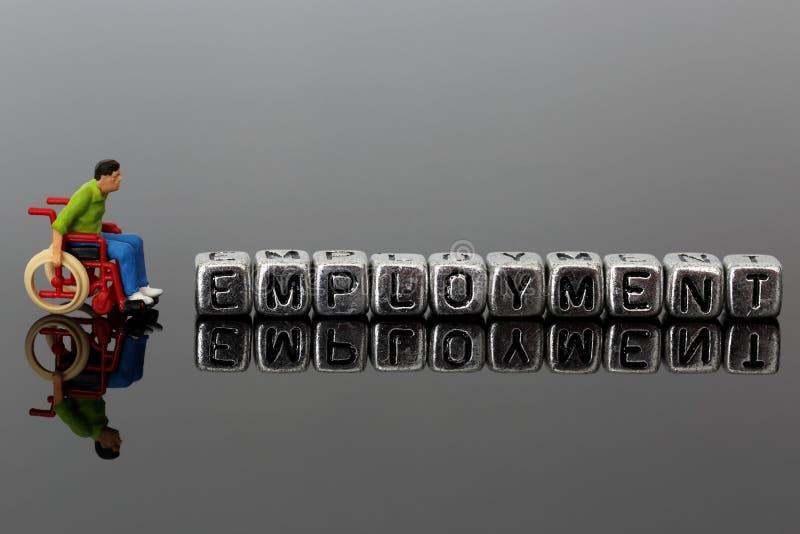 Homme miniature de modèle d'échelle dans un fauteuil roulant avec l'emploi de mot sur des perles image stock