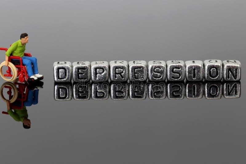 Homme miniature de modèle d'échelle dans un fauteuil roulant avec la dépression de mot sur des perles photographie stock libre de droits
