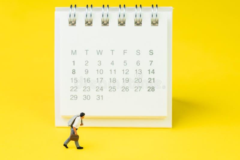 Homme miniature de salaire de bureau d'homme d'affaires de chiffre de personnes marchant et regardant le calendrier de bureau pro images libres de droits