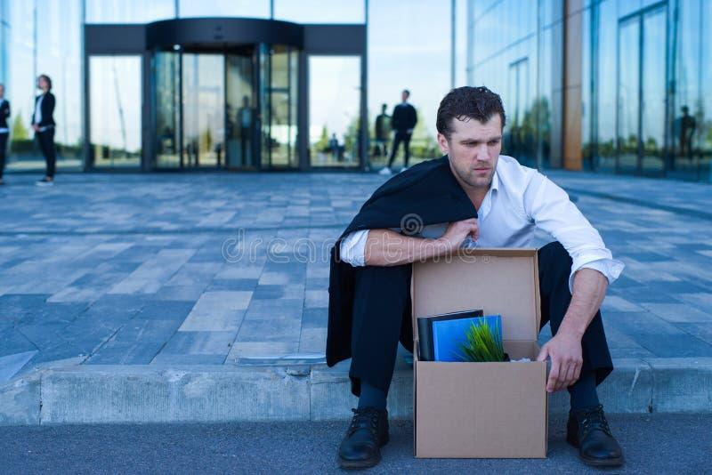 Homme mis le feu d'affaires s'asseyant sur la rue photo stock