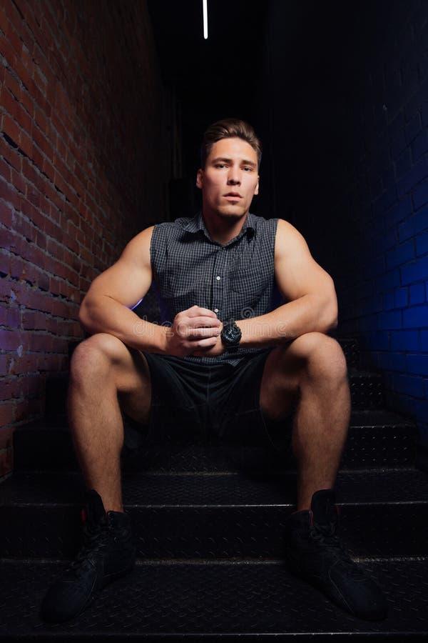 Homme modèle de forme physique dans se reposer de pose sans manche de chemise sur des escaliers dans le grenier de centre de fitn images libres de droits