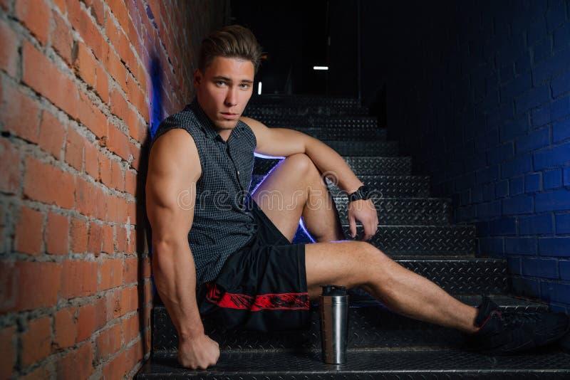 Homme modèle de forme physique dans se reposer de pose sans manche de chemise sur des escaliers dans le grenier de centre de fitn photographie stock libre de droits
