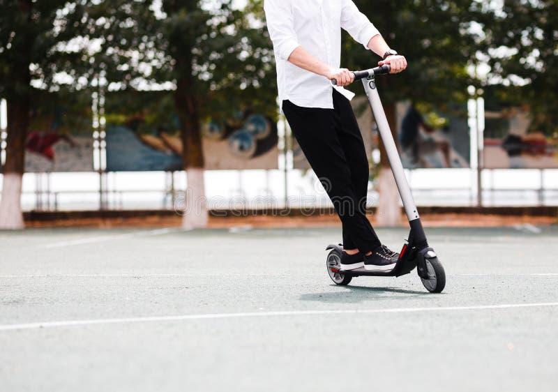 Homme moderne dans l'équipement noir et blanc élégant montant le scooter électrique dans la ville photo stock