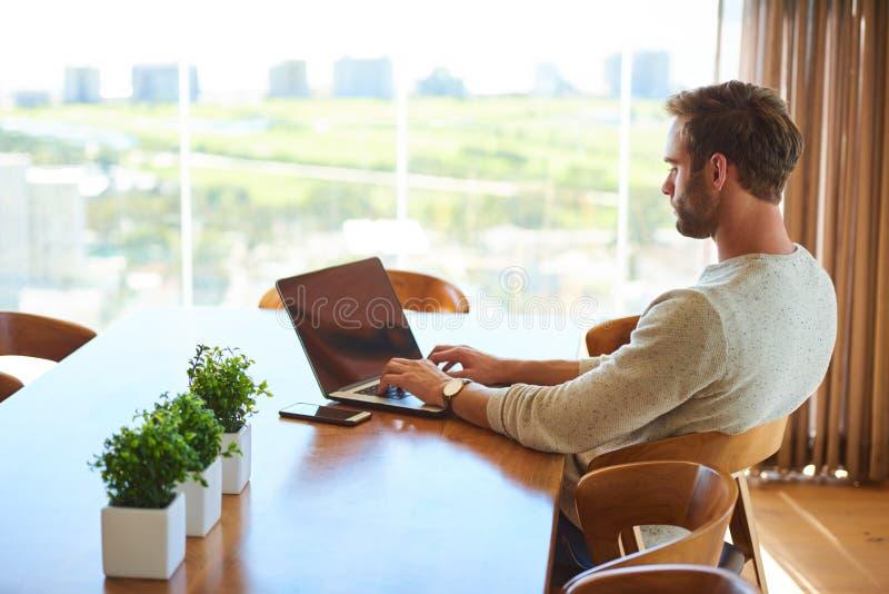 Homme moderne s'asseyant à la table de salle à manger avec son fonctionnement d'ordinateur portable photos stock