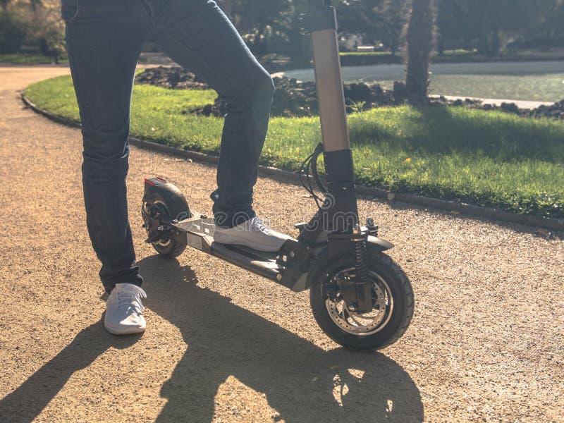Homme moderne sur le scooter électrique en Sunny Park photographie stock