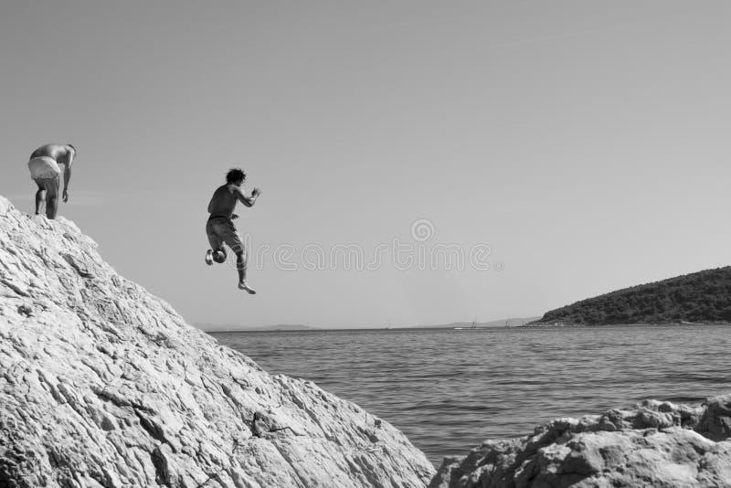 Homme monochrome sautant outre de la roche dans l'eau inconnue photos libres de droits