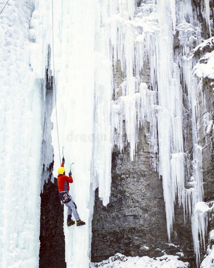 Homme montant la cascade congelée image stock