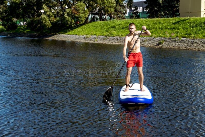 Homme montant un panneau de petite gorgée sur le canal d'aviron de l'eau dans St Petersbu photos stock