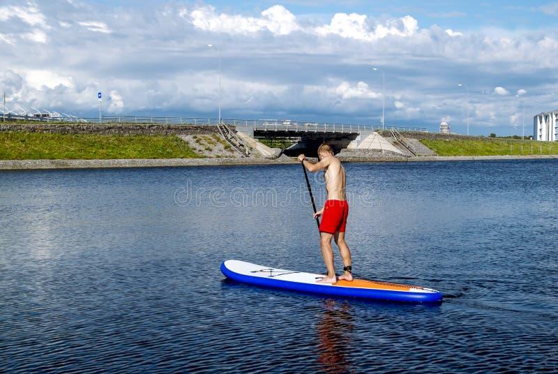 Homme montant un panneau de petite gorgée sur le canal d'aviron de l'eau dans St Petersbu image libre de droits