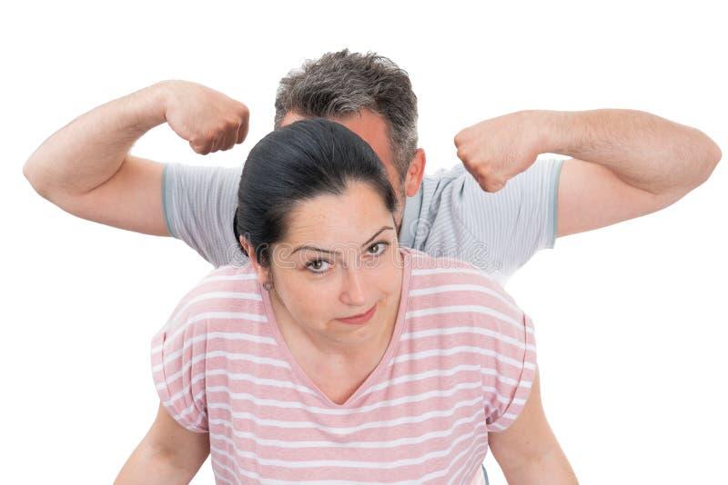 Homme montrant des muscles derrière la femme photographie stock