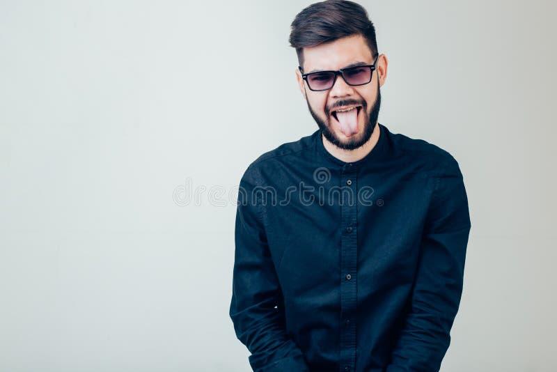Homme montrant sa langue au-dessus de fond gris image stock