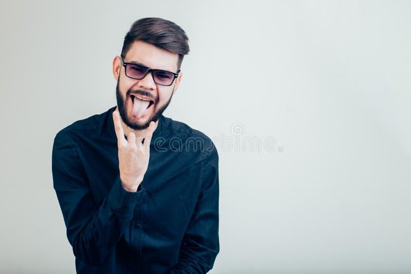 Homme montrant sa langue au-dessus de fond gris images libres de droits