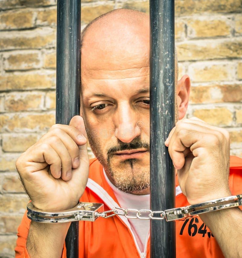 Homme mort marchant - prisonnier triste avec des menottes derrière des barres images stock