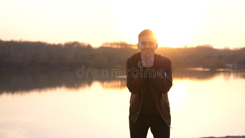 Homme ?motif ?tonn? regardant dans la cam?ra Portrait d'un jeune type beau sur la plage pendant le coucher du soleil photographie stock libre de droits