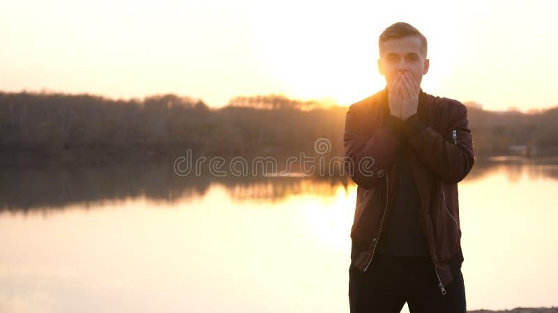 Homme ?motif ?tonn? regardant dans la cam?ra Portrait d'un jeune type beau sur la plage pendant le coucher du soleil images libres de droits