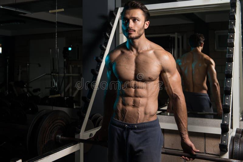 Homme musculaire après l'exercice se reposant dans le gymnase photographie stock