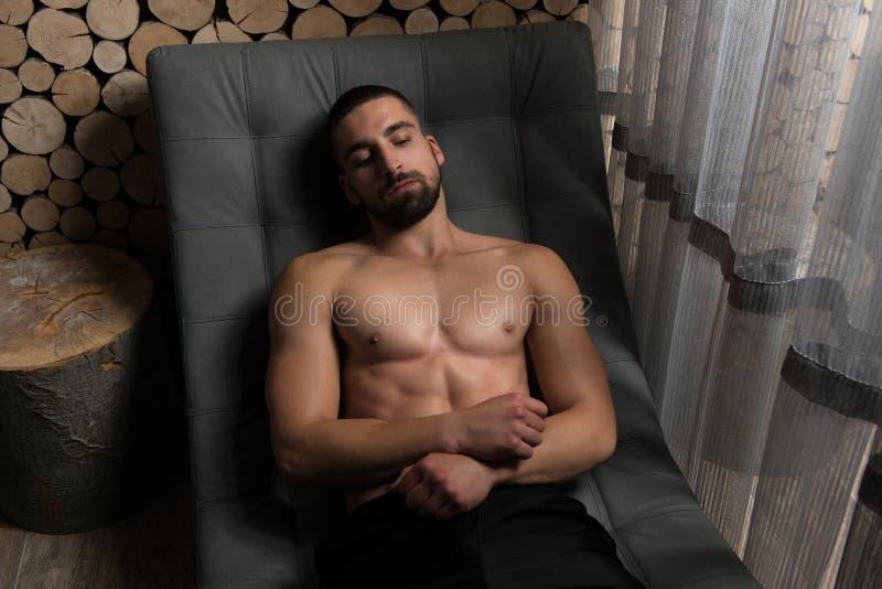 Homme musculaire après l'exercice se reposant sur le fauteuil photo libre de droits