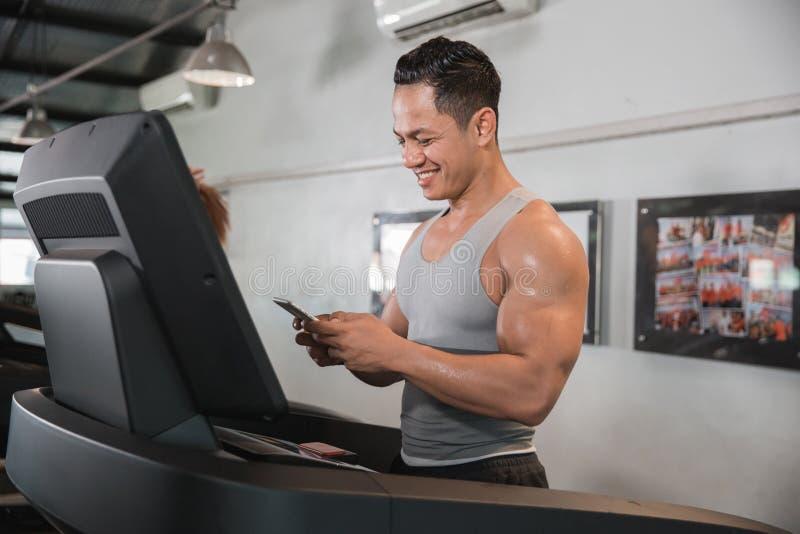 Homme musculaire asiatique sur le tapis roulant tenant le smartphone photos stock