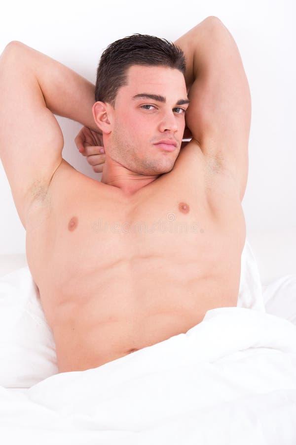 Homme musculaire attirant se situant dans le lit images libres de droits