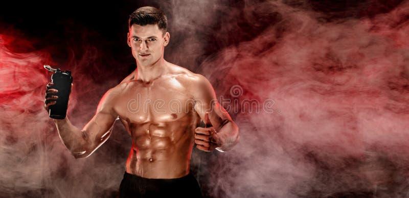 Homme musculaire avec la boisson de protéine dans le dispositif trembleur photos libres de droits