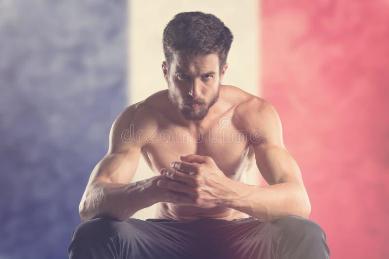 Homme musculaire avec le drapeau français derrière photographie stock libre de droits