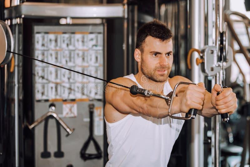 Homme musculaire bel établissant dur au gymnase images stock