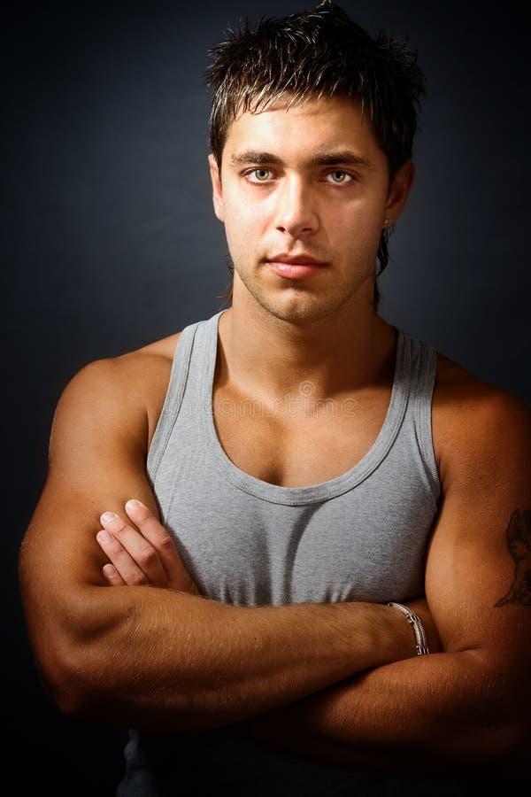 Homme musculaire bel avec des bras pliés photographie stock libre de droits