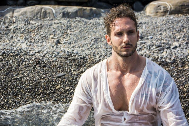 Homme musculaire bel sur la plage s'étendant sur le gravier photo stock
