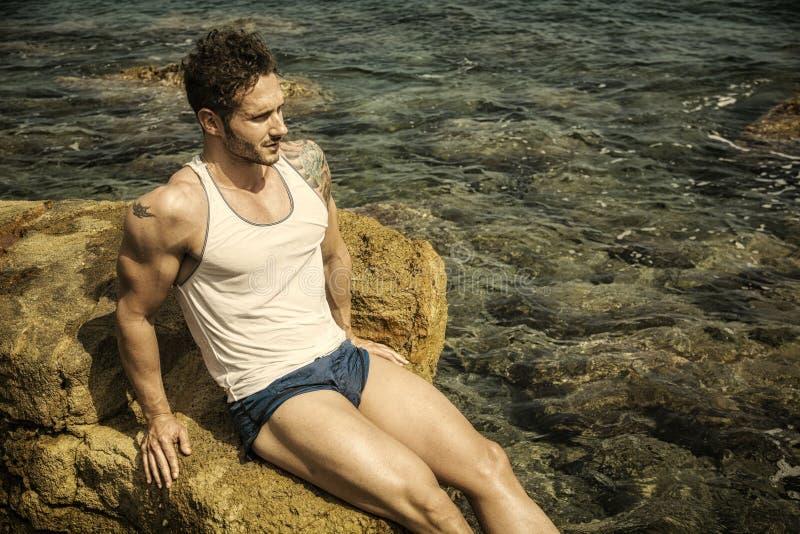 Homme musculaire bel sur la plage se reposant sur des roches image stock