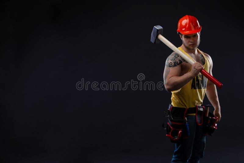 Homme musculaire brutal de travailleur avec un marteau photos stock