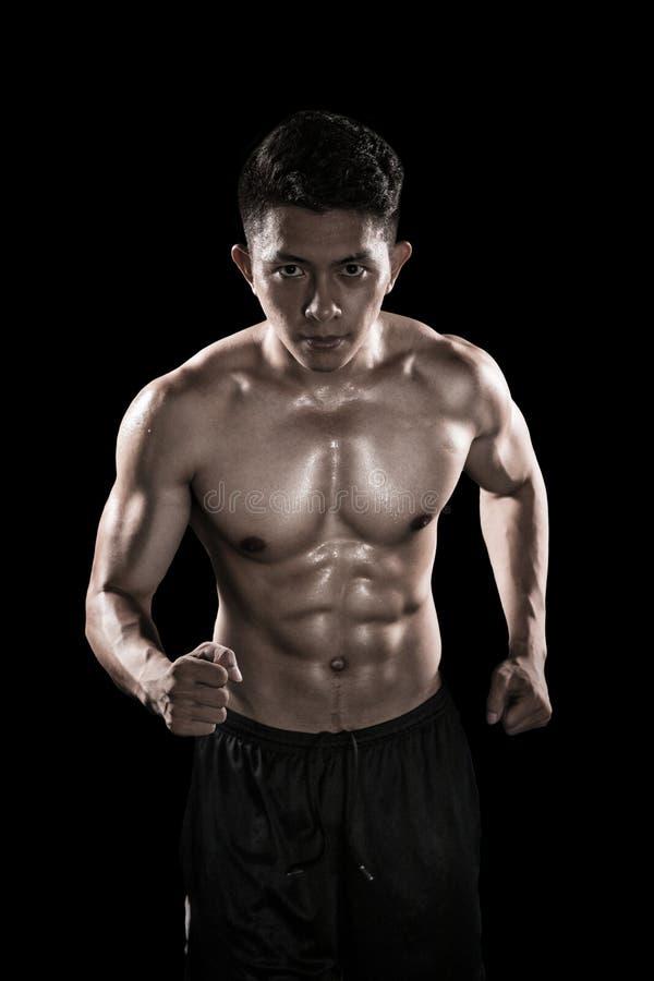 Homme musculaire courant à l'arrière-plan foncé photographie stock