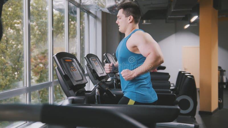 Homme musculaire dans le gymnase - bodybuilder courant sur la voie courante dans le gymnase photos stock