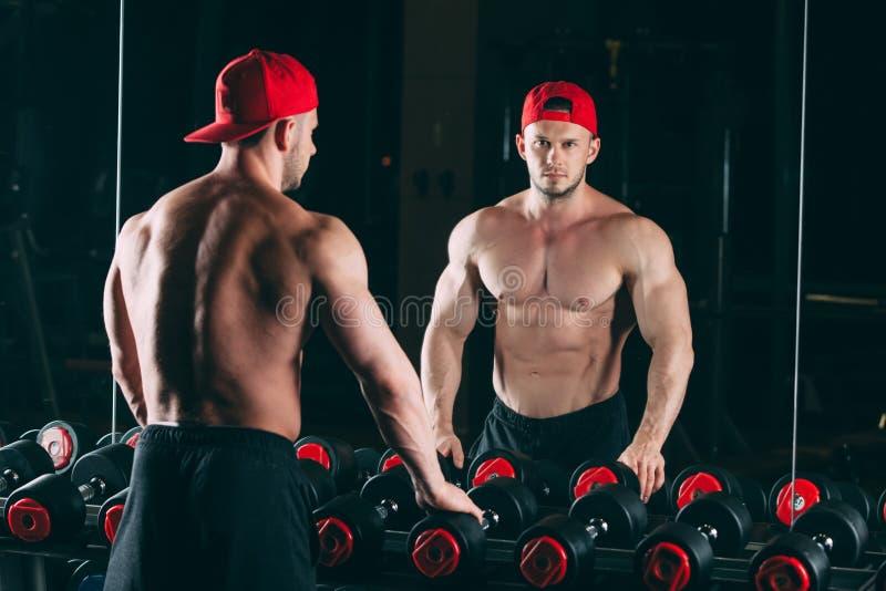 Homme musculaire dans le gymnase tenant les haltères proches, ABS nu masculin fort de torse photographie stock libre de droits
