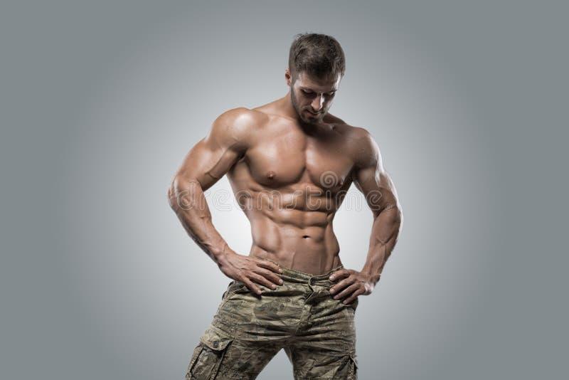 Homme musculaire de bodybuilder d'athlète sur un fond gris image libre de droits