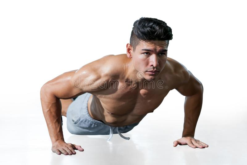 Homme musculaire de bodybuilder faisant l'exercice de pousées d'isolement sur le fond blanc avec le chemin de coupure Jeune sport photographie stock libre de droits