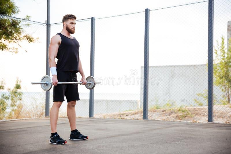 Homme musculaire de forme physique faisant l'exercice lourd utilisant le barbell photos stock