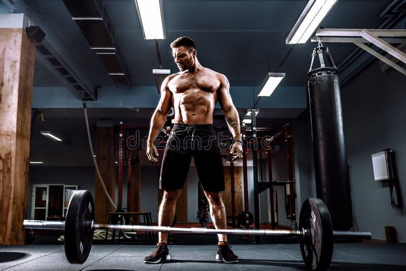 Homme musculaire de forme physique préparant au deadlift un barbell au-dessus de sa tête au centre de fitness moderne Formation f photographie stock