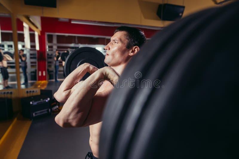 Homme musculaire faisant l'exercice de postures accroupies avec le barbell photo stock