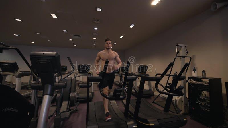 Homme musculaire faisant la cardio- formation sur le tapis roulant dans le mouvement lent de club en bonne santé photo stock