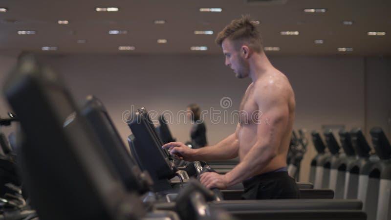 Homme musculaire faisant la cardio- formation sur le tapis roulant dans le mouvement lent de club en bonne santé photos stock