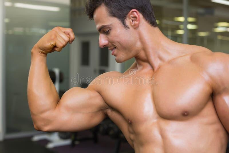 Homme musculaire fléchissant des muscles dans le gymnase image stock