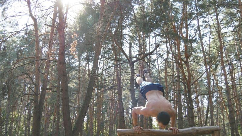 Homme musculaire fort faisant un appui renversé dans un type masculin musculaire de forme physique de forêt faisant des cascades  photo stock
